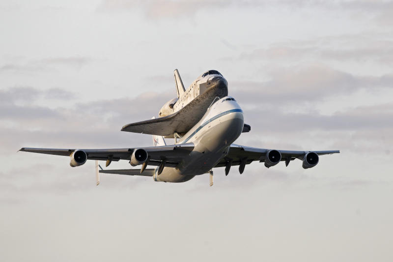 Space shuttle Discovery atop a 747 carrier jet departs the Kennedy Space Center, Tuesday, April 17, 2012, in Cape Canaveral, Fla. Discovery is being transported to the Smithsonian National Air and Space Museum in Washington. The shuttle has been a part of some memorable moments since making its debut in 1984 following shuttles Columbia and Challenger. (AP Photo/John Raoux)