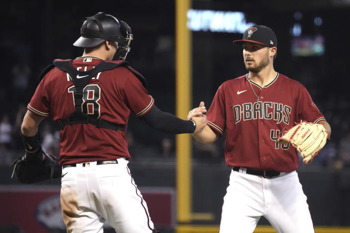 Arizona Diamondbacks catcher Carson Kelly (18) and pitcher Riley Smith celebrate after defeating the St. Louis Cardinals in a baseball game, Sunday, May 30, 2021, in Phoenix. (AP Photo/Rick Scuteri)