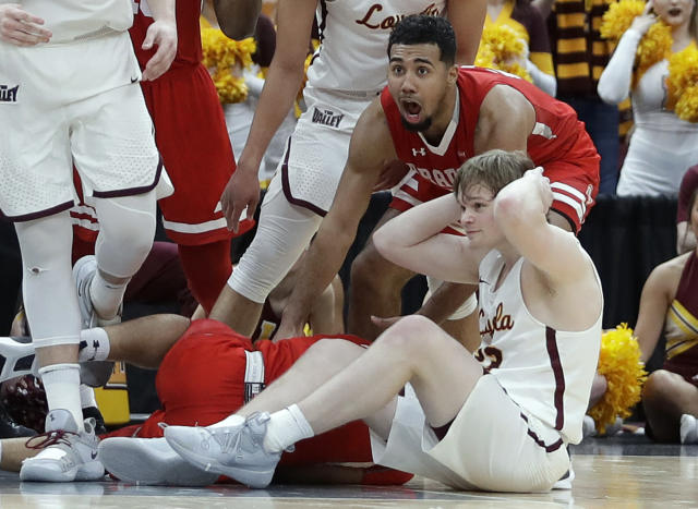 Bradley's Dwayne Lautier-Ogunleye, top, celebrates as Loyola of Chicago's Cooper Kaifes sits on the floor as the final buzzer sounds at the end of an NCAA college basketball game in the semifinal round of the Missouri Valley Conference tournament, Saturday, March 9, 2019, in St. Louis. Bradley won 53-51. (AP Photo/Jeff Roberson)