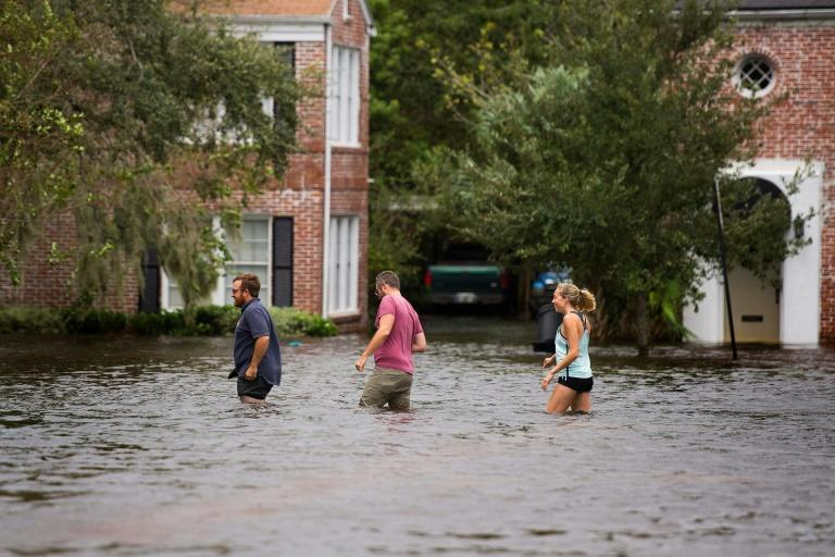 People wade through the flooded streets of the San Marco historic district of Jacksonville, Florida