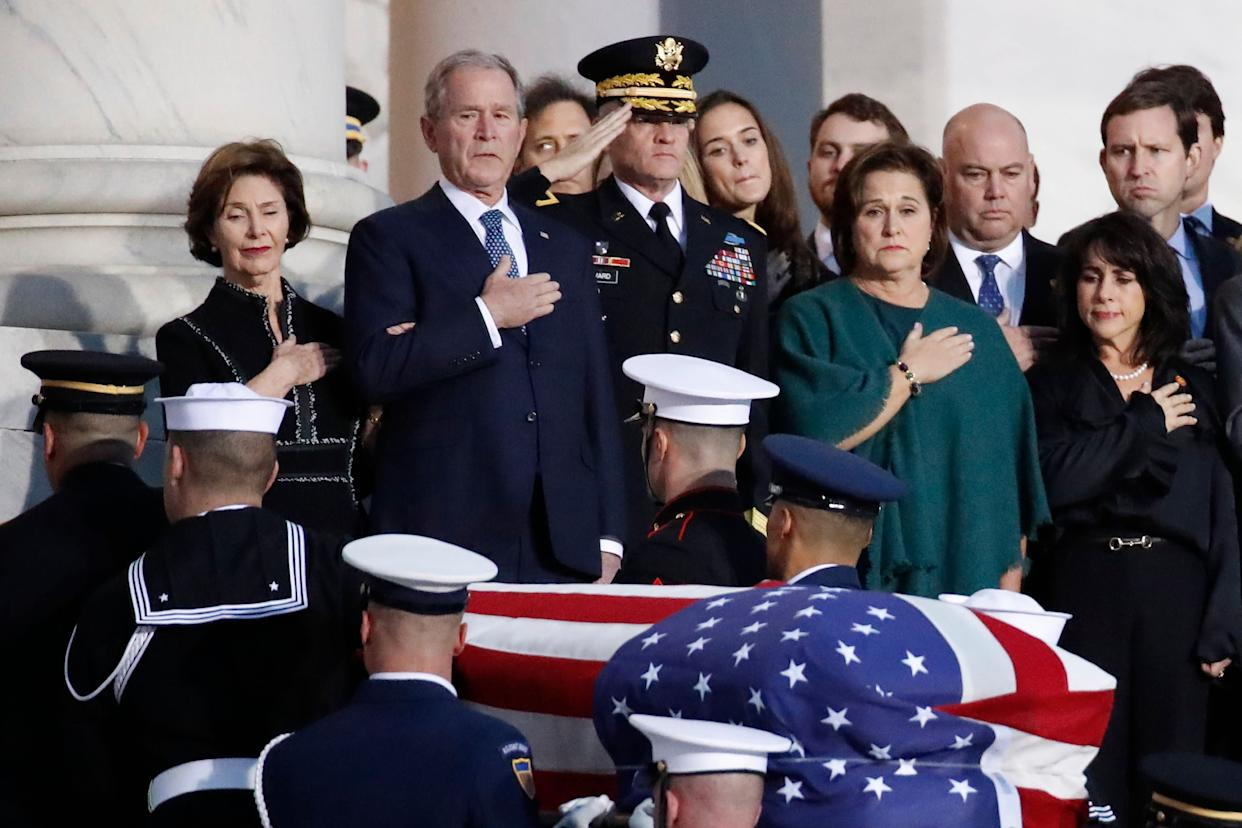 Former President George W. Bush, Laura Bush and other family members watch as a military honor guard carries George H.W. Bush's casket into the Capitol.