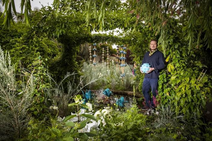 """Landscape designer and ceramist Dustin Gimbel holds a pollen grain created for his """"Sculptura Botanica"""" exhibition at the Sherman Library & Gardens. <span class=""""copyright"""">(Allen J. Schaben / Los Angeles Times)</span>"""