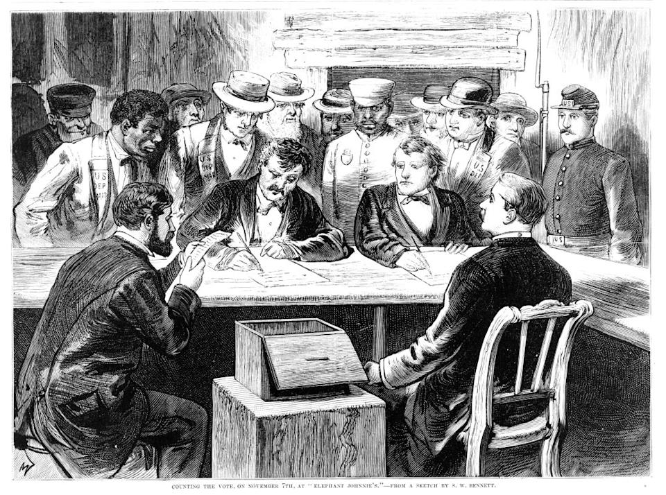 """Men seated around a table with a ballot box counting votes after the disputed 1876 presidential election at 'Elephant Johnnie's', a New Orleans bar and polling place, Nov. 7, 1876. From Frank Leslie's Illustrated Newspaper.<span class=""""copyright"""">Library of Congress/Getty Images</span>"""