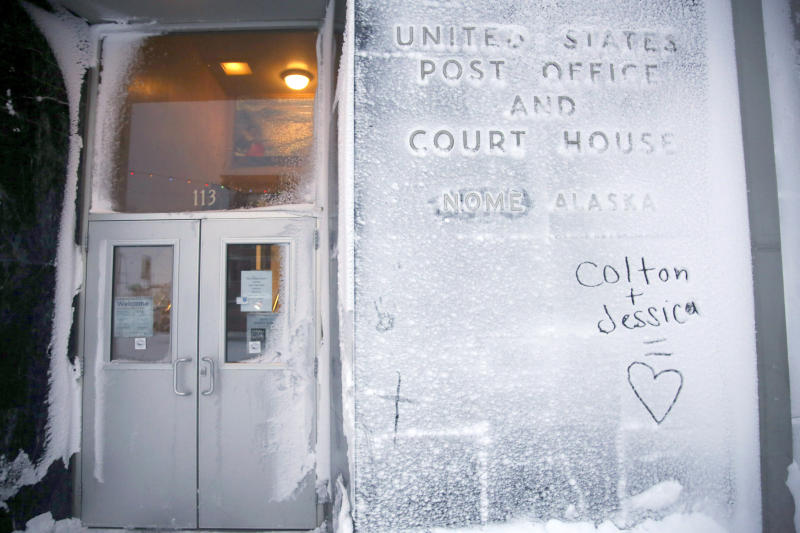 In this Feb. 13, 2019, photo, the names of two lovers are etched onto a snow covered wall of the United States Post Office and Court House in Nome, Alaska. (AP Photo/Wong Maye-E)