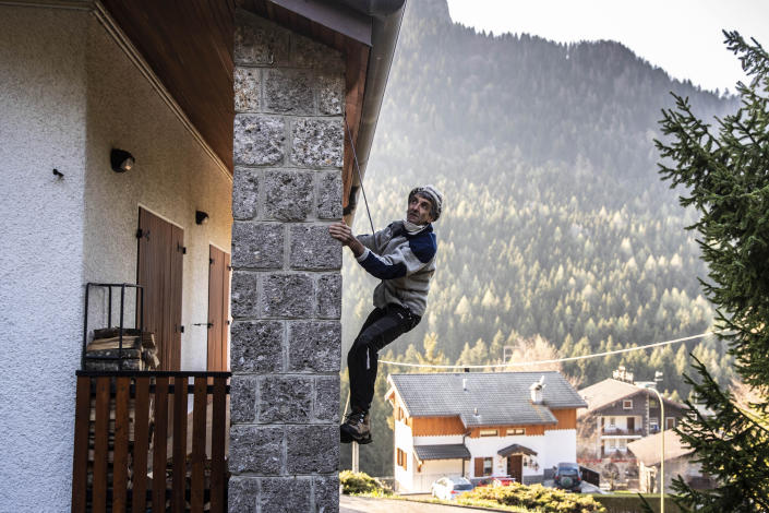 """In this image taken on Thursday, April 23, 2020, alpine guide Ernesto Cocchetti, 57, climbs the external facade of his house in Castione Della Presolana, near Bergamo, northern Italy. Cocchetti predicts a return to """"living with nature's rhythms"""" once government restrictions to prevent the spread of COVID-19 will be eased. (AP Photo/Luca Bruno)"""