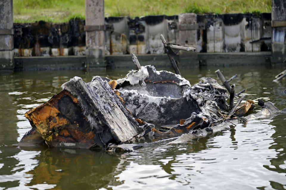 Part of a shrimp boat, one of several that caught fire and burned during Hurricane Ida, lies in the channel of Delta Marina in Plaquemines Parish, La., Monday, Sept. 13, 2021. The wrecked boats, docks and processing equipment left by Hurricane Ida has some wondering what the future holds for Louisiana's seafood industry. (AP Photo/Gerald Herbert)