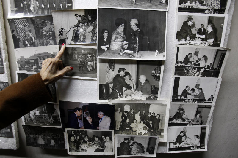 """In this Nov. 26, 2012 photo, journalist and radio host Maria Julia Venegas, better known as Maruja Venegas, 97, points to pictures of herself during an interview at her home in Lima, Peru. Venegas who began broadcasting """"Radio Club Infantil,"""" a show for Peru's children in the golden age of radio and World War II, has earned a citation from Guinness World Records as the globe's longest-running radio personality. (AP Photo/Karel Navarro)"""