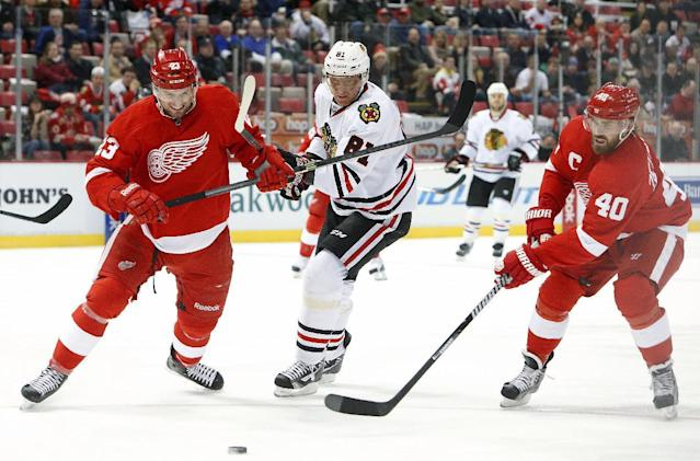 Detroit Red Wings defenseman Brian Lashoff (23) battles with Chicago Blackhawks right wing Marian Hossa (81), of the Czech Republic, and Henrik Zetterberg (40), of Sweden, in the first period of an NHL hockey game Wednesday, Jan. 22, 2014, in Detroit. (AP Photo/Paul Sancya)