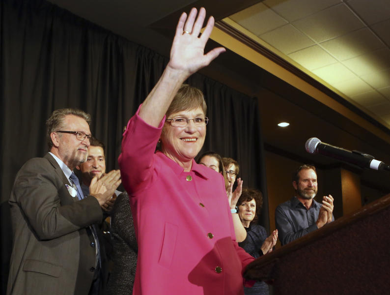 Democrat Laura Kelly waved to the crowd at the Ramada Hotel and Convention Center in Topeka after she won election Tuesday, Nov. 6, 2018, to become the next Kansas governor. On the left is her running mate Lynn Rogers. (Thad Allton /The Topeka Capital-Journal via AP)