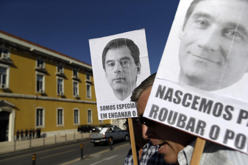 """Protestors hold photos of Portugal's Finance Minister Vitor Gaspar and Prime Minister Pedro Passos Coelho, right, outside the finance ministry in Lisbon Wednesday, Oct. 3 2012.  A few dozen protestors blew horns and whistles while inside the building new austerity measures were announced by the minister in a news conference. Captions on the posters read """"we're specialists in cheating the people"""" and """"born to rob the people"""".  Portugal is tightening its belt another notch, with the government announcing steep income tax hikes to reduce the bailed-out country's debt load despite mounting discontent over austerity measures. (AP Photo/Armando Franca)"""
