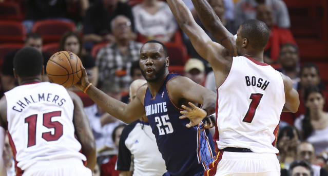 Miami Heat players Mario Chalmbers (15) and Chris Bosh (1) force Charlotte Bobcatd' Al Jefferson (25) to pass the ball off during the first half of an NBA basketball game in Miami, Monday, March 3, 2014. (AP Photo/J Pat Carter)