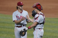 Philadelphia Phillies starting pitcher Aaron Nola, left, and catcher J.T. Realmuto congratulate each other after they defeated the Miami Marlins in a baseball game, Friday, Sept. 11, 2020, in Miami. (AP Photo/Wilfredo Lee)
