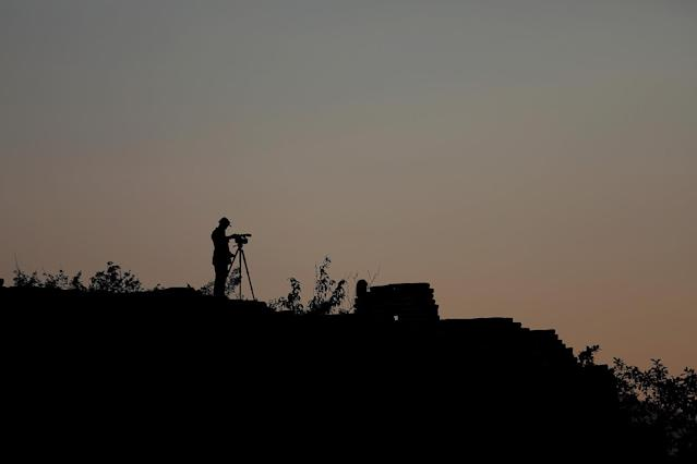 <p>A cameraman documenting the reconstruction project of the Jiankou section of the Great Wall, films as the sun rises over the wall, located in Huairou District, north of Beijing, China, June 7, 2017. (Photo: Damir Sagolj/Reuters) </p>