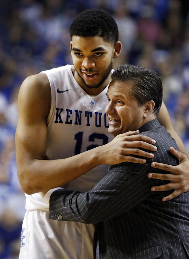 Kentucky's Karl-Anthony Towns, left, gets a hug from head coach John Calipari during the second half of an NCAA college basketball game against Georgia, Tuesday, Feb. 3, 2015, in Lexington, Ky. Kentucky won 69-58. (AP Photo/James Crisp)