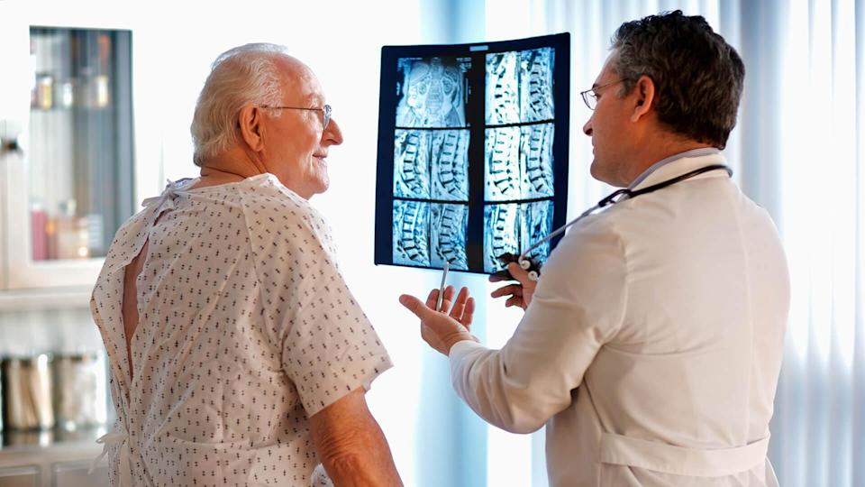 Doctor talking to senior male patient while holding up MRI.