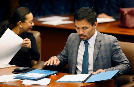 Philippine Senator and boxing champion Manny Pacquiao reads his briefing materials next to fellow Senator Grace Poe, as he prepares for the Senate session in Pasay city, Metro Manila, Philippines September 20, 2016. Picture taken September 20, 2016.    REUTERS/Erik De Castro