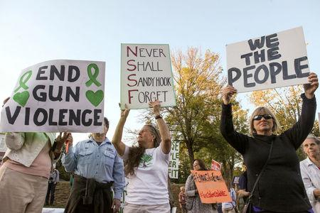 FILE PHOTO:    Mourners hold signs during a solidarity vigil in memory of victims of Las Vegas' Route 91 Harvest music festival mass killing, in Newtown, Connecticut U.S., the site of the 2012 Sandy Hook school shooting,  October 4, 2017. REUTERS/Michelle McLoughlin/File Photo