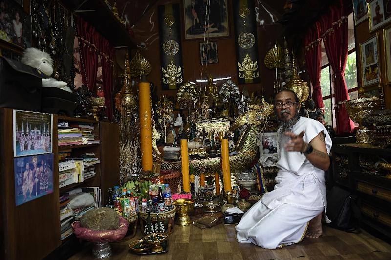 Surrounded by a cornucopia of glittering Buddha statues, eerie dolls and other spiritual trinkets, the 57-year-old Thai 'hermit' Toon uses powders and ointments to conduct his 'good luck' ritual. (AFP Photo/Lillian SUWANRUMPHA)