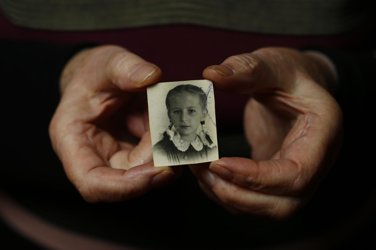 Auschwitz death camp survivor Barbara Doniecka, 80, who was registered with camp number 86341, holds up wartime photo of herself, as she poses for a photograph in Warsaw January 12, 2015. Doniecka was 12-years-old during the Warsaw Uprising when she was sent to Pruszkow camp. She was then sent by train to Auschwitz-Birkenau. As the liberation of Auschwitz approaches its 70th anniversary this month, Reuters photographers took portraits of now elderly survivors. About 1.5 million people, most of them Jews, were killed at the Nazi camp which has became a symbol of the horrors of the Holocaust and World War Two, which ravaged Europe. The camp was liberated by Soviet Red Army troops on January 27, 1945 and about 200,000 camp inmates survived. REUTERS/Kacper Pempel (POLAND - Tags: ANNIVERSARY SOCIETY PORTRAIT CONFLICT)