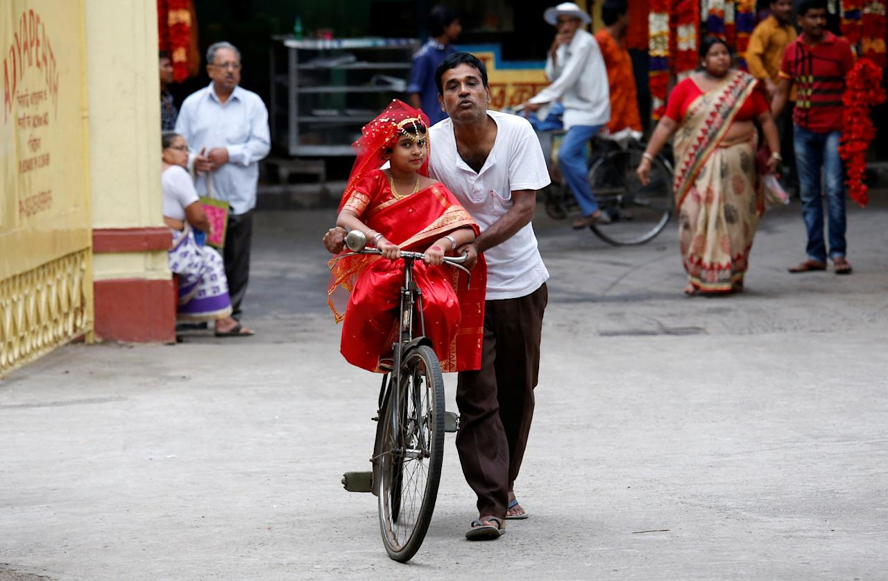 <p>A man carries his daughter, dressed as Kumari, on a bicycle, as they arrive to attend rituals to celebrate the Navratri Festival, inside the Adyapeath Temple, on the outskirts of Kolkata, India April 5, 2017. REUTERS/Rupak De Chowdhuri </p>