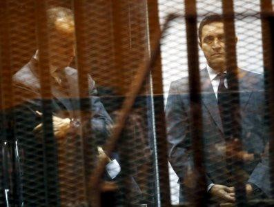 FILE PHOTO: Gamal (L) and Alaa Mubarak, sons of Egypt's former president Hosni Mubarak, react behind bars during their trial with their father (not pictured) inside a dock at the police academy, on the outskirts of Cairo, May 9, 2015. REUTERS/Amr Abdallah Dalsh