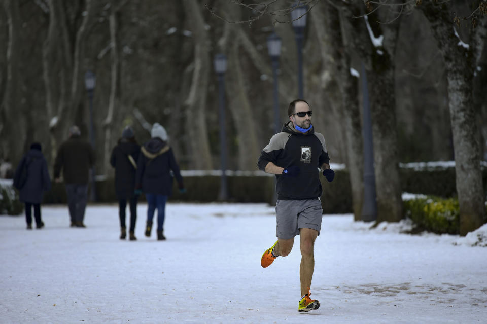 A man jog, after the recent snow fall, in Pamplona, northern Spain, Sunday, Jan. 10, 2021. Emergency crews in central Spain have cleared 500 roads and rescued over 1,500 people stranded in vehicles as the country shovels out of its worst snowstorm in recent memory. (AP Photo/Alvaro Barrientos)