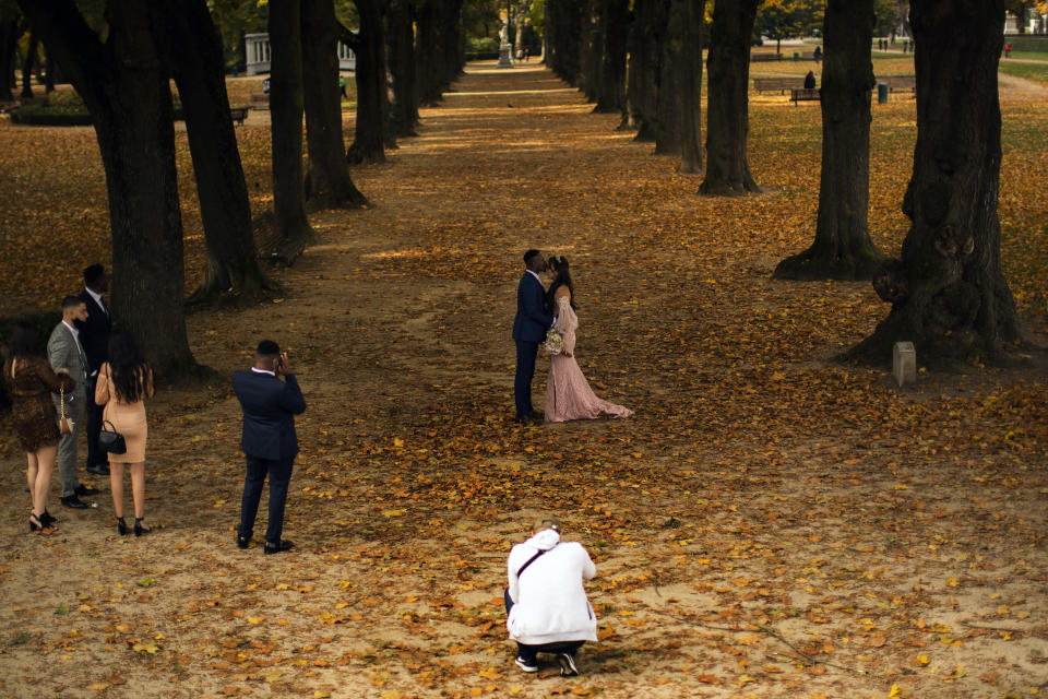A couple wearing wedding outfits pose for photos at Cinquantenaire park in an autumn day in Brussels, Friday, Oct. 23, 2020. Belgian Prime Minister Alexander De Croo stopped short Friday of imposing another full lockdown, as the country did in March, but introduced a series of new restrictive measures as the number of COVID-19 related hospital admissions and deaths continue to soar. (AP Photo/Francisco Seco)