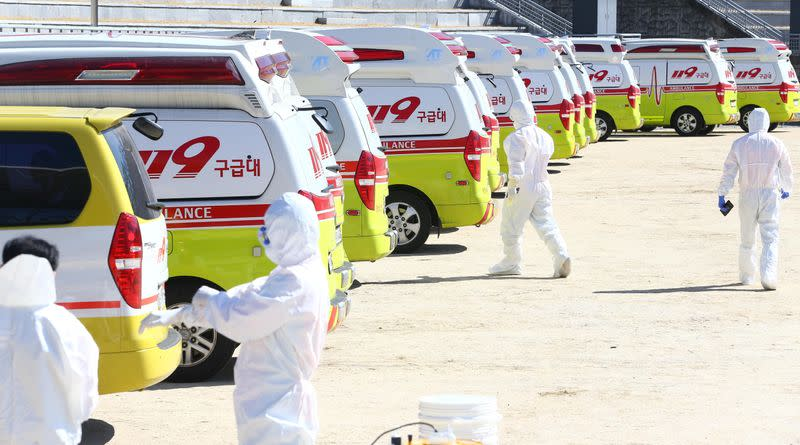 Medical workers get ready as ambulances are parked to transport a confirmed coronavirus patient in Daegu