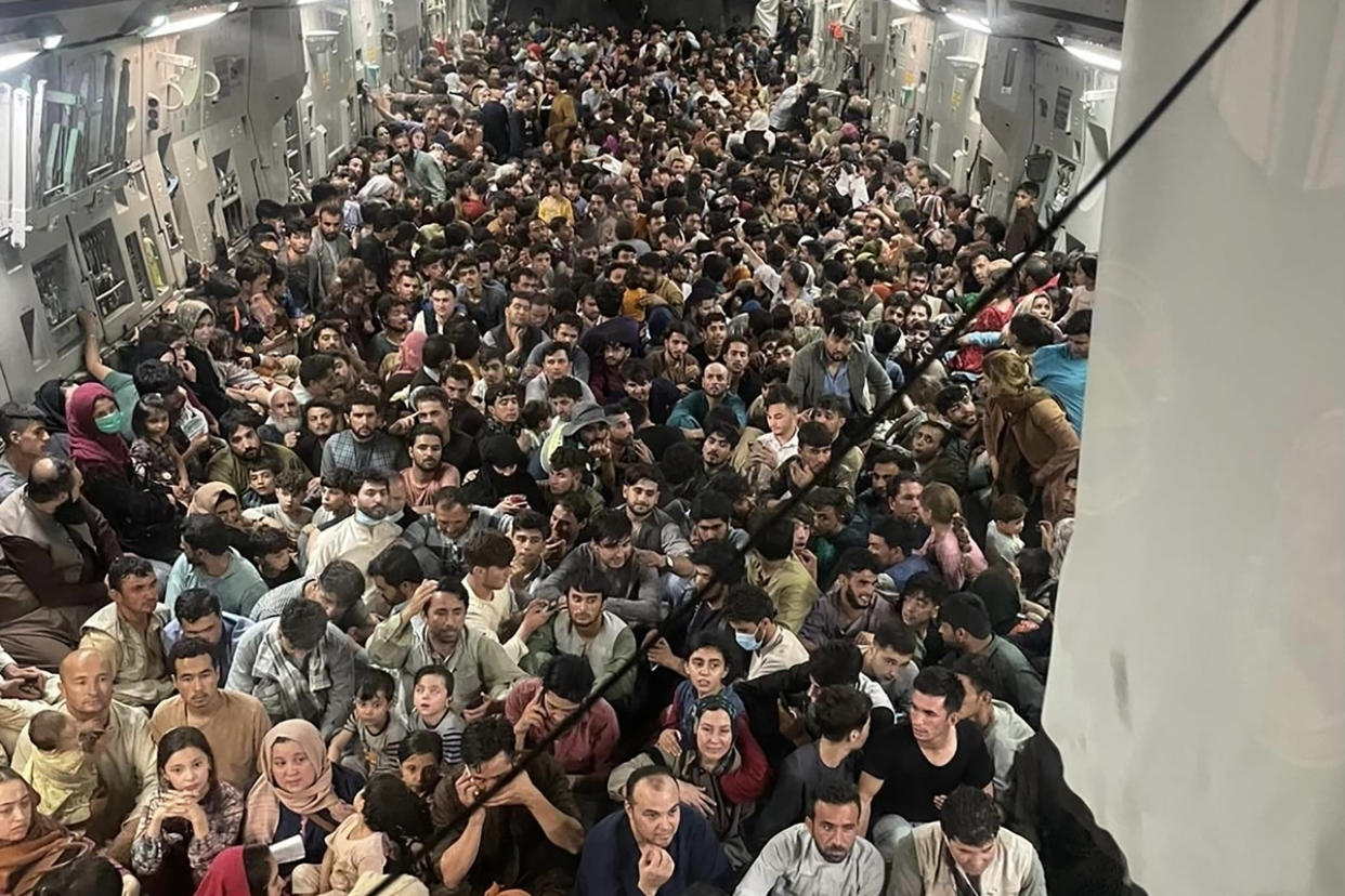 TOPSHOT - This image distributed Courtesy of the US Air Force shows the inside of Reach 871, a U.S. Air Force C-17 Globemaster III flown from Kabul to Qatar on August 15, 2021. The plane safely evacuated some 640 Afghans from Kabul late Sunday, according to U.S. defense officials contacted by Defense One. Tens of thousands of people have tried to flee Afghanistan to escape the hardline Islamist rule expected under the Taliban, or fearing direct retribution for siding with the US-backed government that ruled for the past two decades. Evacuation flights from Kabul's airport restarted on Tuesday after chaos the previous day in which huge crowds mobbed the tarmac, with some people so desperate they clung to the outside of a US military plane as it prepared for take-off.     - RESTRICTED TO EDITORIAL USE - MANDATORY CREDIT