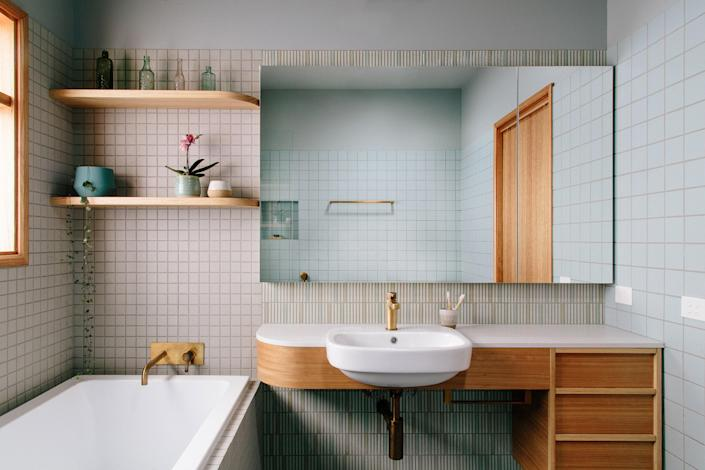 """AFTER: Megan was inspired by a 1960s pool for the bathroom's renovation, and sourced tiles from Artedomus and Academy Tiles for the walls and tub enclosure. """"Many of this project's features, such as the curved vanity, were functionally important and became some of the most beautiful aspects of the design,"""" she says."""
