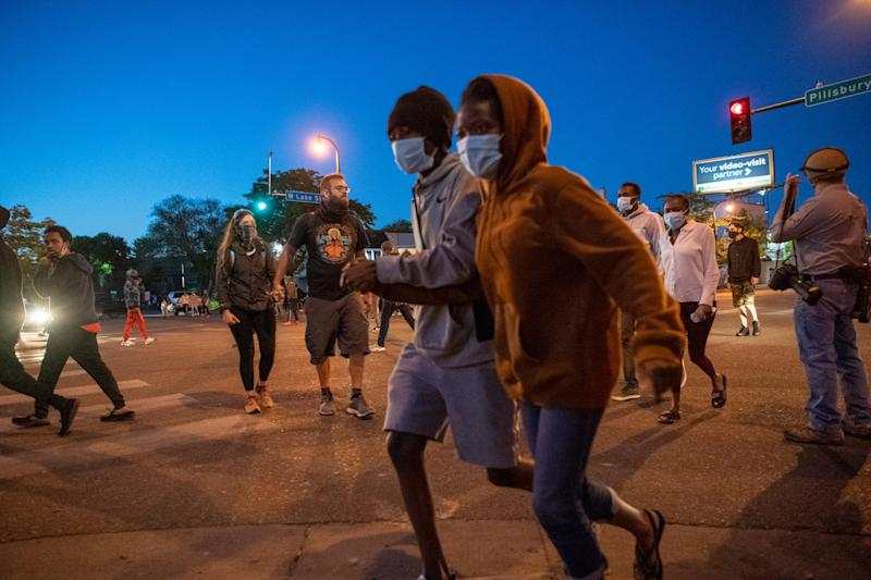 Demonstrators run during protests in Minneapolis on Saturday, May 30, 2020.