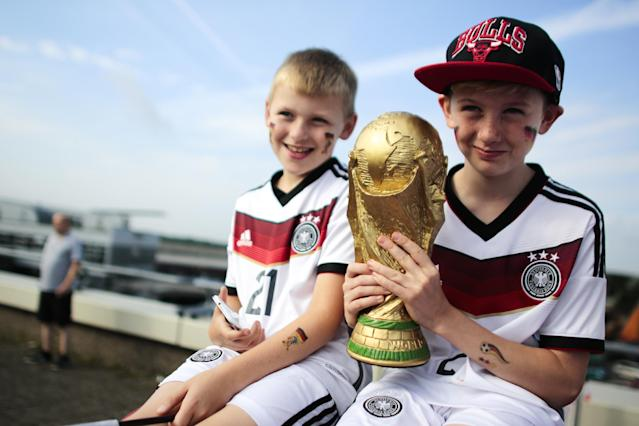 Two boys pose for a photo with a copy of the World Cup trophy as they waits at the airport Tegel to welcome German national soccer team in Berlin Tuesday, July 15, 2014. Germany beat Argentina 1-0 on Sunday to win its fourth World Cup title. (AP Photo/Markus Schreiber)