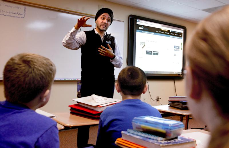 In this March 18, 2014 photo Motif Investing founder Hardeep Walia talks with sixth grade students at Oak Grove Middle School in Fargo, North Dakota. Sixth grade teacher Dave Carlson started a competition between regular and advance math classes at Oak Grove and registered his students with Motif Investing, a company that enables customers to buy baskets of stocks. In the end, Carlson's regular math class yielded a nearly 22 percent gain and trounced every university club participating in a contest that was held at the same time. (AP Photo/Bruce Crummy)