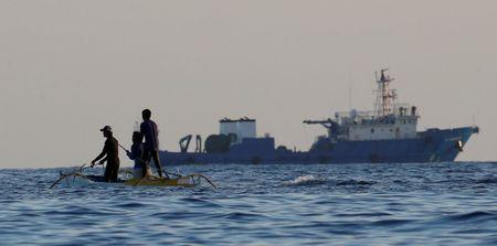 Filipino fishermen past a large Chinese vessel at the disputed Scarborough Shoal