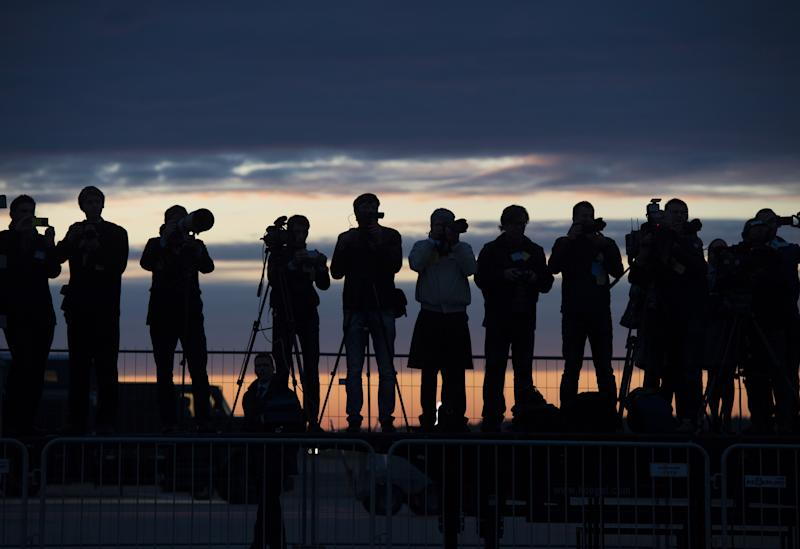 Estonian press photographers cover the arrival of US President Barack Obama on Air Force One at sunrise in Tallinn, Estonia, September 3, 2014