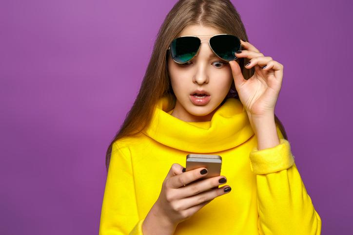 A woman in a yellow sweater shocked as she looks at her phone.
