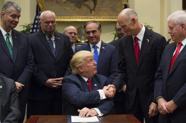 U.S. President Donald Trump, center, shakes hands with Rick Scott, governor of Florida, after signing bill S. 544, the Veterans Choice Program Extension and Improvement Act, in the Roosevelt Room of the White House in Washington, D.C., U.S., on Wednesday, April 19, 2017 The bill extends a program allowing eligible veterans to seek medical care from private health-care providers. (Photo: Molly Riley/Pool via Bloomberg)