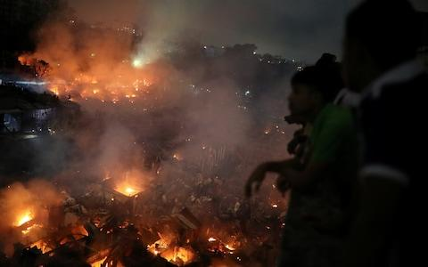 People gather at a rooftop to watch the fire that broke out at a slum in Dhaka, - Credit: REUTERS/Mohammad Ponir Hossain