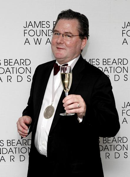 FILE - In this May 7, 2012 file photo, chef Charlie Trotter poses with a glass of champagne and his medal for Humanitarian of the Year during the James Beard Foundation Awards in New York. On Tuesday, Nov. 5, 2013, Chicago and Cook County officials announced that Trotter has died. The award-winning chef died a year after closing his eponymous Chicago restaurant that is credited with elevating the city's cuisine and providing a training ground for some of the nation's other best chefs. (AP Photo/Jason DeCrow, File)