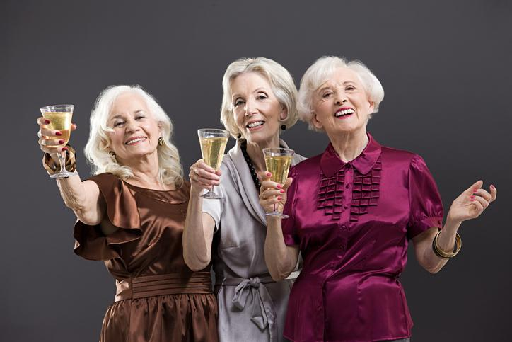 Three elderly female friends toasting with champagne.