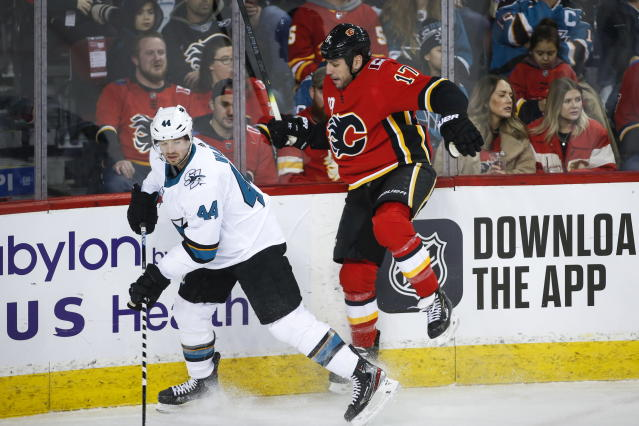 San Jose Sharks' Marc-Edouard Vlasic, left, dodges a check from Calgary Flames' Milan Lucic during the first period of an NHL hockey game, Tuesday, Feb. 4, 2020 in Calgary, Alberta. (Jeff McIntosh/The Canadian Press via AP)