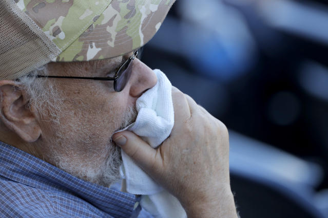 A spectator uses a towel to cover his mouth as he watches the ninth inning of a spring training baseball game between the New York Yankees and the Washington Nationals, Thursday, March 12, 2020, in West Palm Beach, Fla. Major League Baseball is delaying the start of its season by at least two weeks because of the coronavirus outbreak and has suspended the rest of its spring training game schedule. (AP Photo/Julio Cortez)