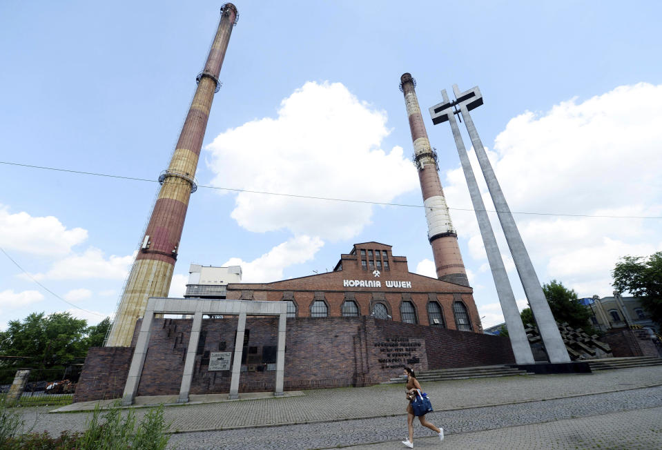 A woman walks by the closed Wujek coal mine in Katowice, Poland, Saturday, July 4, 2020. The coronavirus has ripped through Poland's coal mines, where men descend deep underground in tightly packed elevators and work shoulder-to-shoulder. The virus hot spots, centered in the southern Silesia region, have paralyzed an already-troubled industry, forcing many to stay home from work and triggering a three-week closure of many state-run mines. (AP Photo/Czarek Sokolowski)