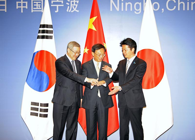 China's Foreign Minister Yang Jiechi, center, Japanese Foreign Minister Koichiro Gemba, right, and South Korean Foreign Minister Kim Sung-hwan pose for a photo before the start of the 6th Trilateral Foreign Ministers Meeting between China, Japan and South Korea in the eastern Chinese city of Ningbo Sunday, April 8, 2012. (AP Photo/Peter Parks, Pool)