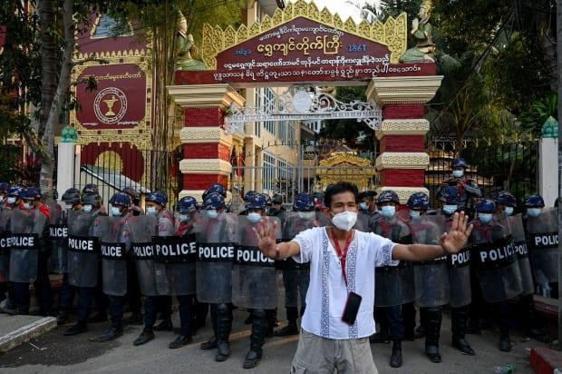 A man gestures towards residents, unseen, as police stand guard at the entrance gate of a Buddhist monastery where pro-military supporters took shelter after clashes with local residents following a demonstration against the military coup in Yangon on Thursday.