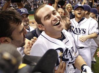 The Rays mobbed Evan Longoria after his game-winning home run on Wednesday. Dan Johnson (right) had kept Tampa Bay alive with a home run of his own in the ninth inning
