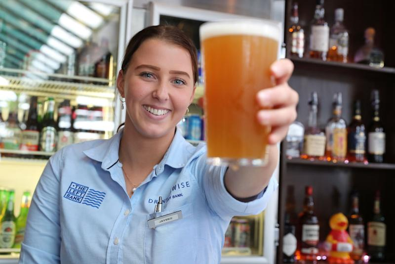 FREMANTLE, AUSTRALIA - JUNE 06: Bar staff member Jaymee Elliot passes over a pint of beer at the Left Bank after re-opening on June 06, 2020 in Fremantle, Australia. Restrictions continue to ease around Australia in response to the country's declining COVID-19 infection rate. Phase three of eased coronavirus restrictions have come into effect across Western Australia as of midnight 6 June 2020, with the majority of businesses affected by the lockdown permitted to reopen, including gyms, theatres, beauty services and cinemas. Indoor and outdoor gatherings of up to 100 people are also now permitted and up to 300 people will be allowed in some venues subject to spacing rules, while food businesses and licensed premises can operate with seated service. Full contact sport and training is now permitted while playgrounds, skate parks and outdoor gym equipment can be used. Most intrastate travel restrictions have been lifted and Rottnest Island has reopened to visitors again. (Photo by Paul Kane/Getty Images)