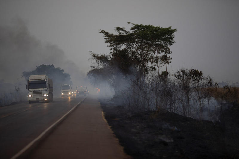 Trucks drive alongside scorched fields on the BR163 highway in the Nova Santa Helena municipality, in the state of Mato Grosso, Brazil (Picture: AP)