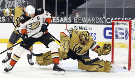 Vegas Golden Knights goalie Marc-Andre Fleury blocks a shot as Anaheim Ducks center Ryan Getzlaf (15) looks for a rebound during the first period of an NHL hockey game Saturday, Jan. 16, 2021, in Las Vegas. (AP Photo/Isaac Brekken)