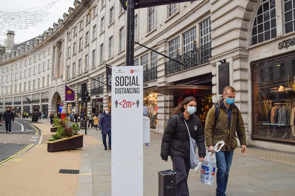 People wearing face masks walk past a social distancing sign on Regent Street, which was blocked for vehicle traffic for a day. London has seen an increase in coronavirus cases, prompting fears that tougher restrictions may be introduced once again. (Photo by Vuk Valcic / SOPA Images/Sipa USA)